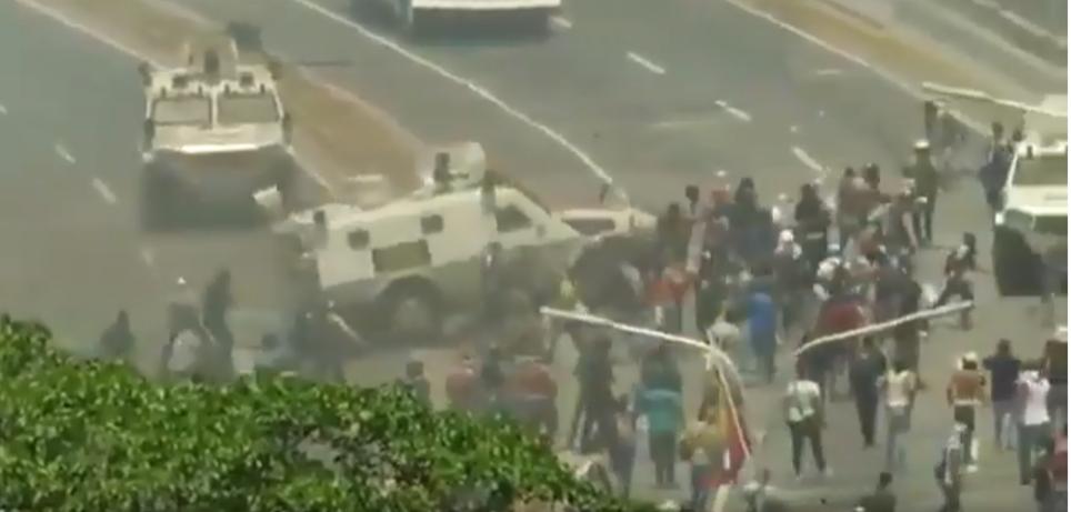 omento em que tanques da Guarda Nacional Bolivariana avançam contra manifestantes na Venezeula